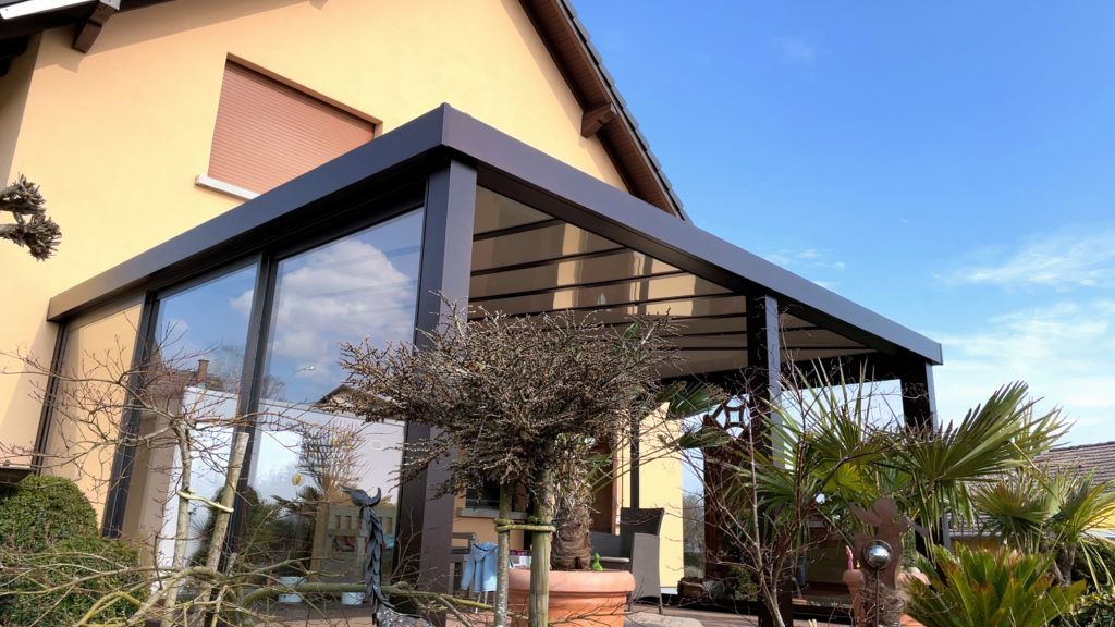 Auvent accolé à une maison avec des fermetures latérales en vitres coulissantes sur les côtés